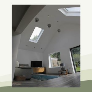 Inside the extension. It is spacious and light, with a high pitched ceiling and modern light fittings. Light pours through a window in the pitched roof, with even more light provided by a picture window and glass doors which lead into the garden outside.