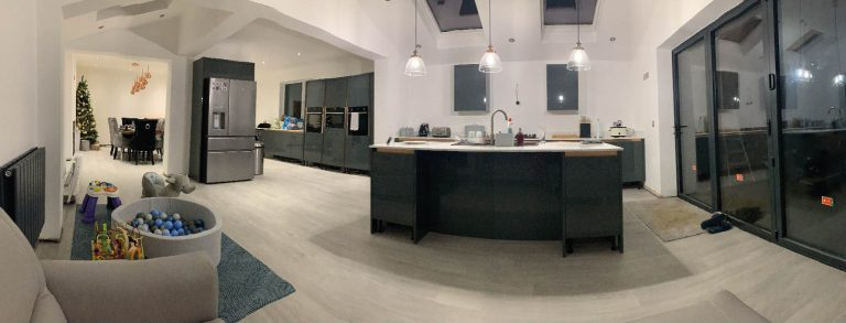 A wide angle photograph of a completed extension. On the right is a large modern kitchen with floor to ceiling windows and a glass door leading to the garden. Skylights and modern hanging light fittings provide even more light into the space. On the left is a large dining area with table and chairs.