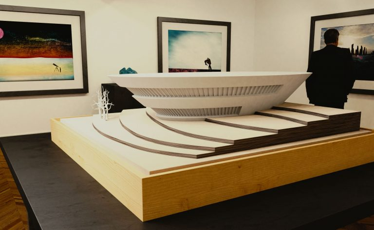 A white model of a modern building is displayed on a black table in the middle of an art gallery.
