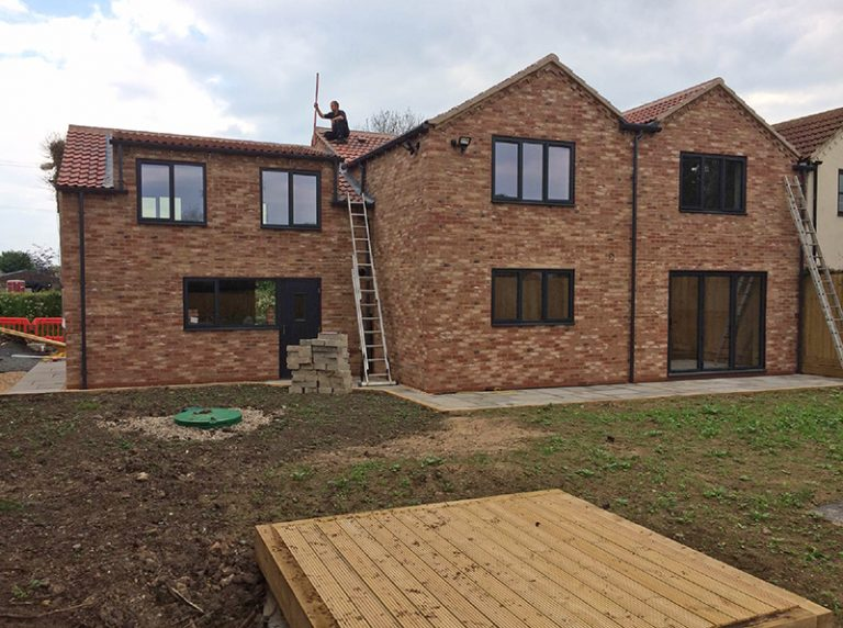 An almost-completed new-build home. The home sits in front of a large garden, and includes large windows, patio doors, and high-quality brickwork. A man sits on the roof finishing his work.