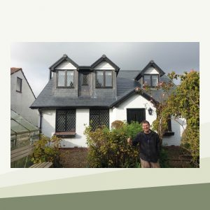 The front of the cottage showing two new dormers on the roof level which complement the original design of the house and blend with its existing features. A man stands outside smiling with a thumbs up.