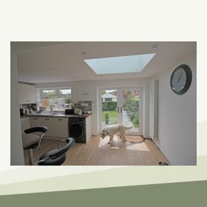 The inside of the extension facing the double doors. It is bright and spacious, with a kitchen on the left-hand side. Light pours in through the skylight, and a dog stands in its warmth.